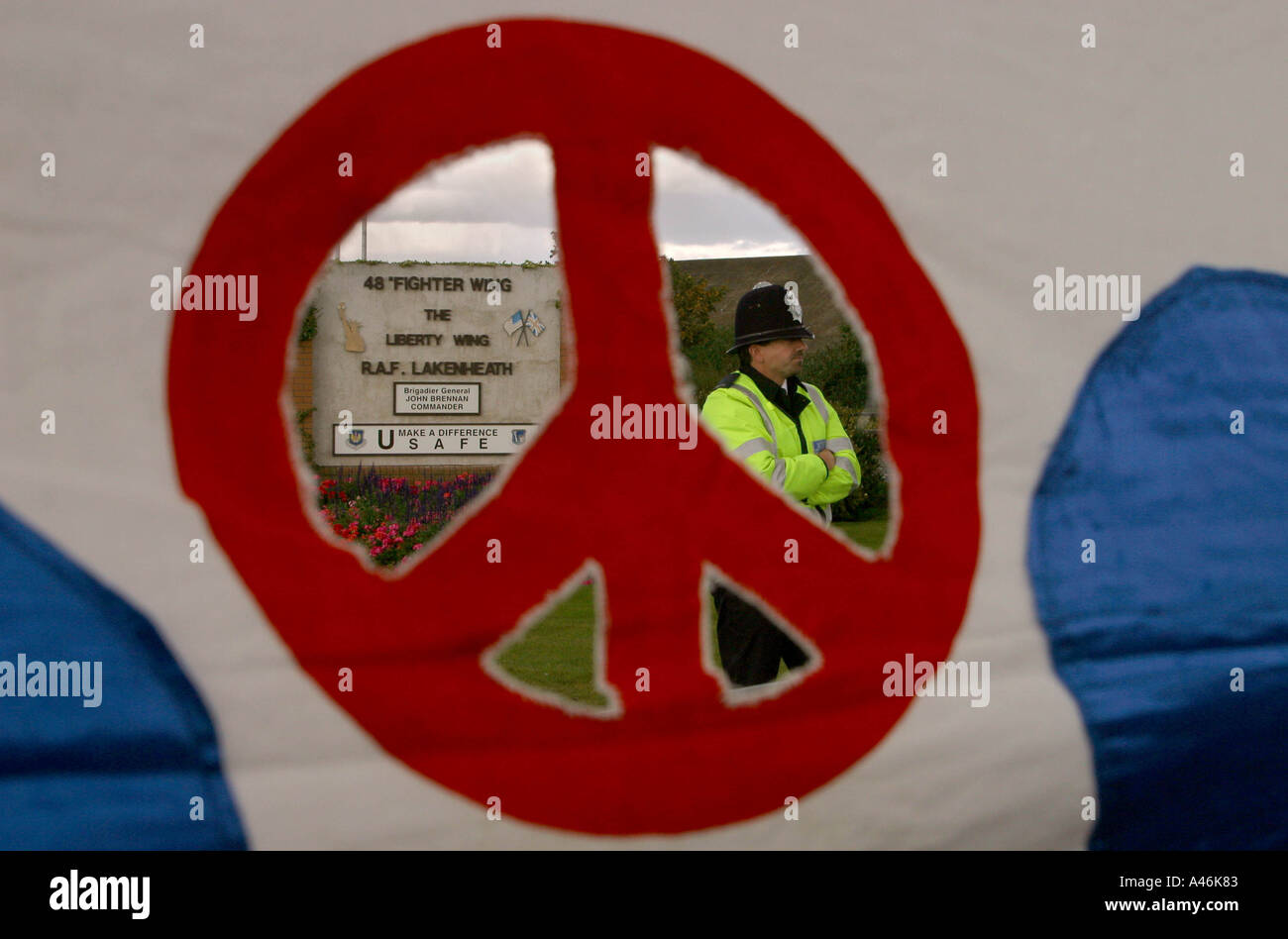 peace demonstration at lakenheath airbase a policeman at the entrance to lakenheath airbase is seen through a campaign for nuclear disarmament banner at a vigil and demonstration outside the airbase in suffolk england 7 october 2002 the airbase is the home of the united states airforce 48th fighter wing using f1 11 fighter bombers which will be deployed in any forthcoming military action against iraq the base also stores an undisclosed number of nuclear weapons - Stock Image