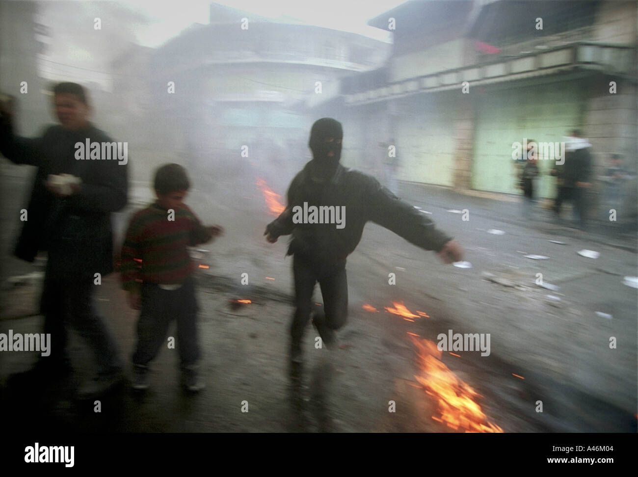 hebron stonethrowers palestinian boys throw stones at the israeli army through a cloud of teargas during a clash in hebron on the west bank 3rd december 2000 after a martyrs funeral during the second intifada - Stock Image