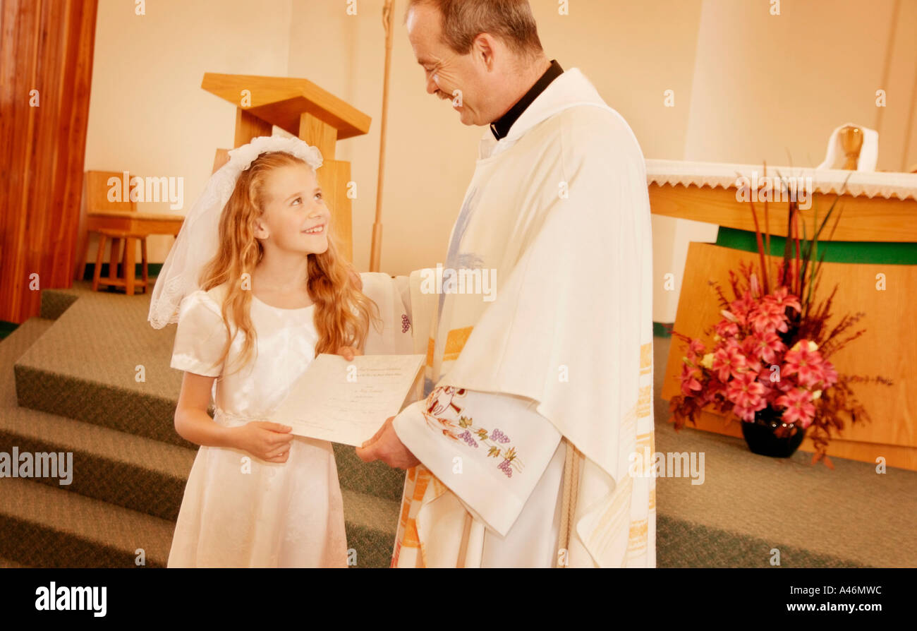 Child receives certificate from Priest - Stock Image