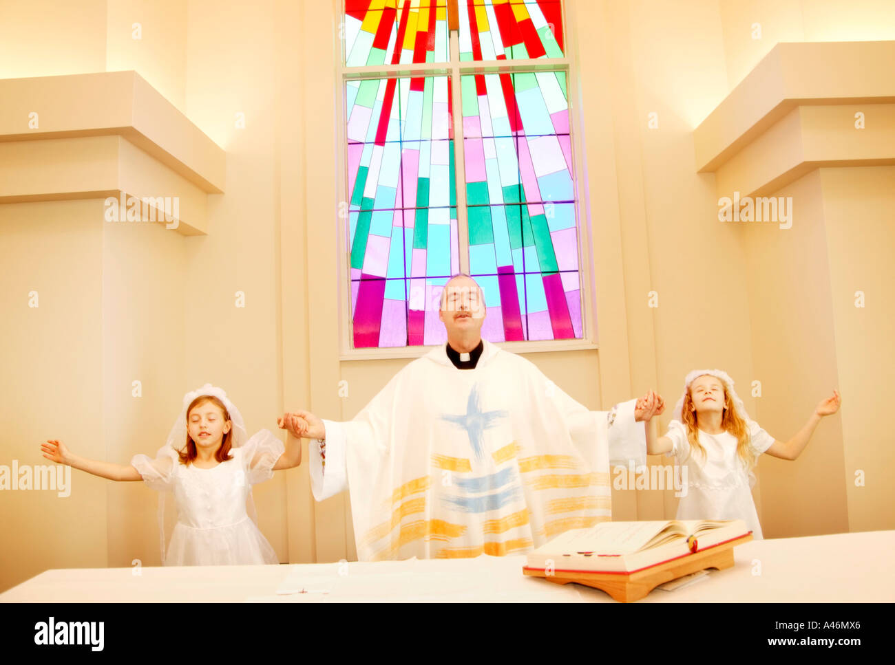 Priest with girls on first communion - Stock Image