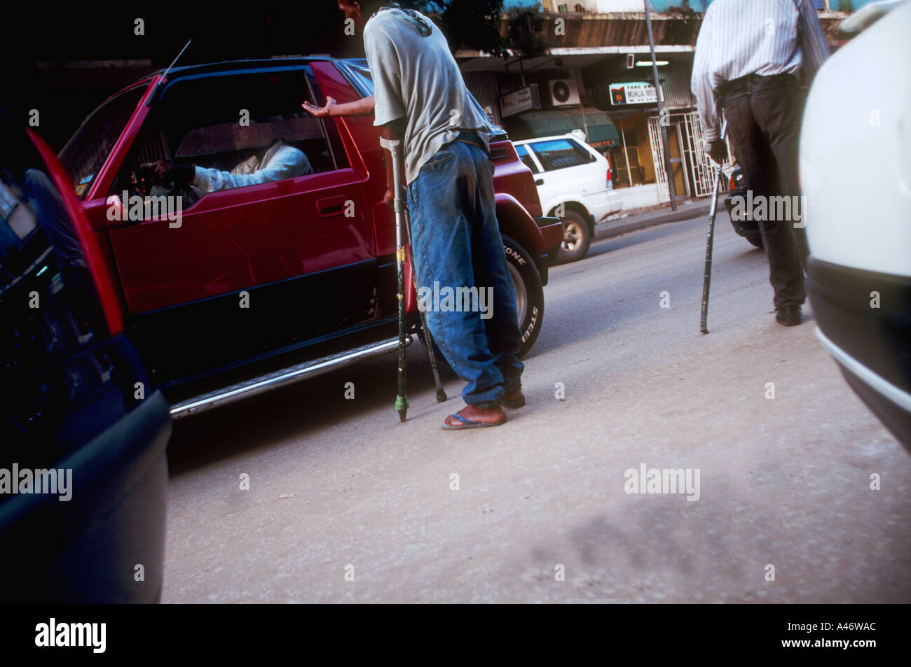 Dasilio and his friend, both injured during the civil war, beg from wealthy Luandans in their cars. Luanda, Angola - Stock Image