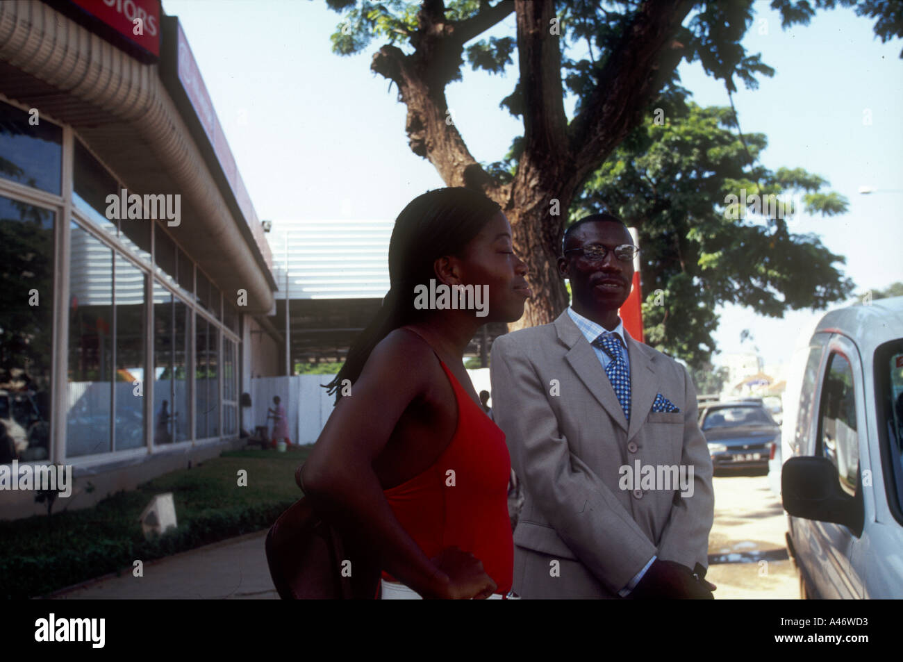 A wealthy, well dressed young Luandan couple wait by their car in Luanda, Angola - Stock Image