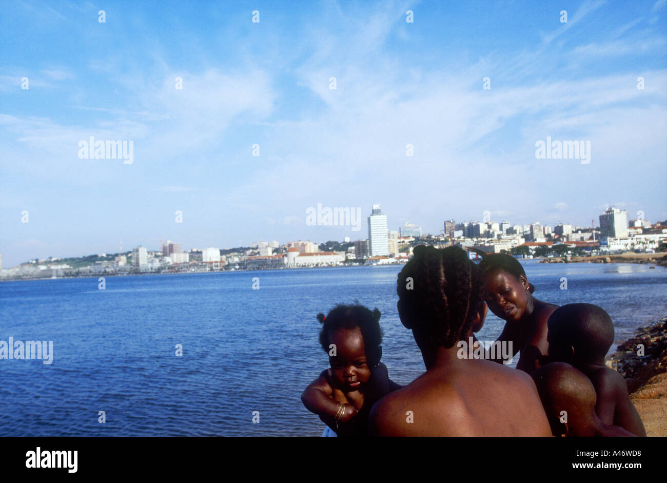 Poor mothers from a nearby slum come to play with their children on the beach on the Marginal, Luanda Angola - Stock Image
