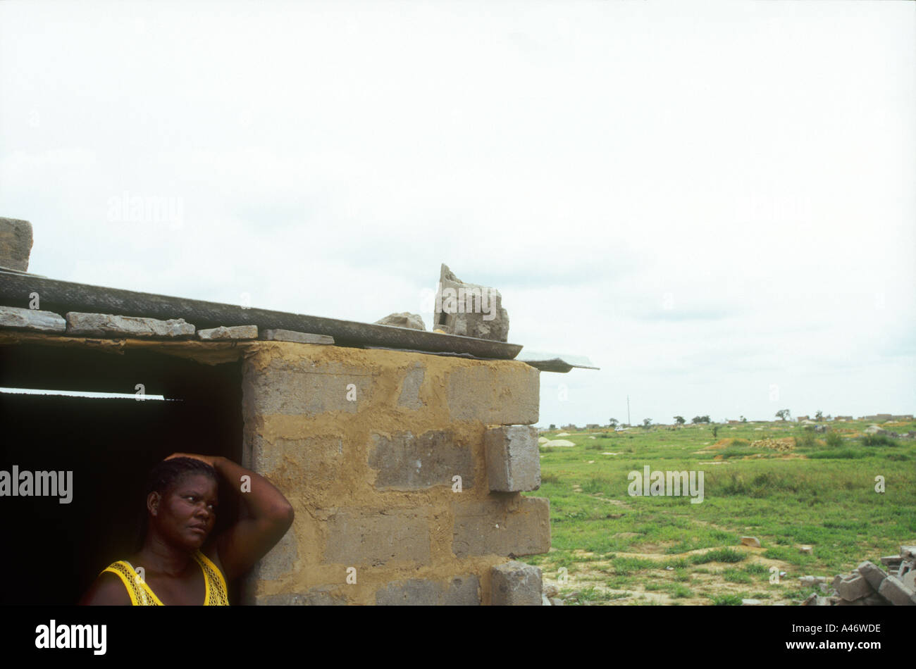 A woman stands in the ruins of her house that was demolished by government thugs Luanda, Angola - Stock Image