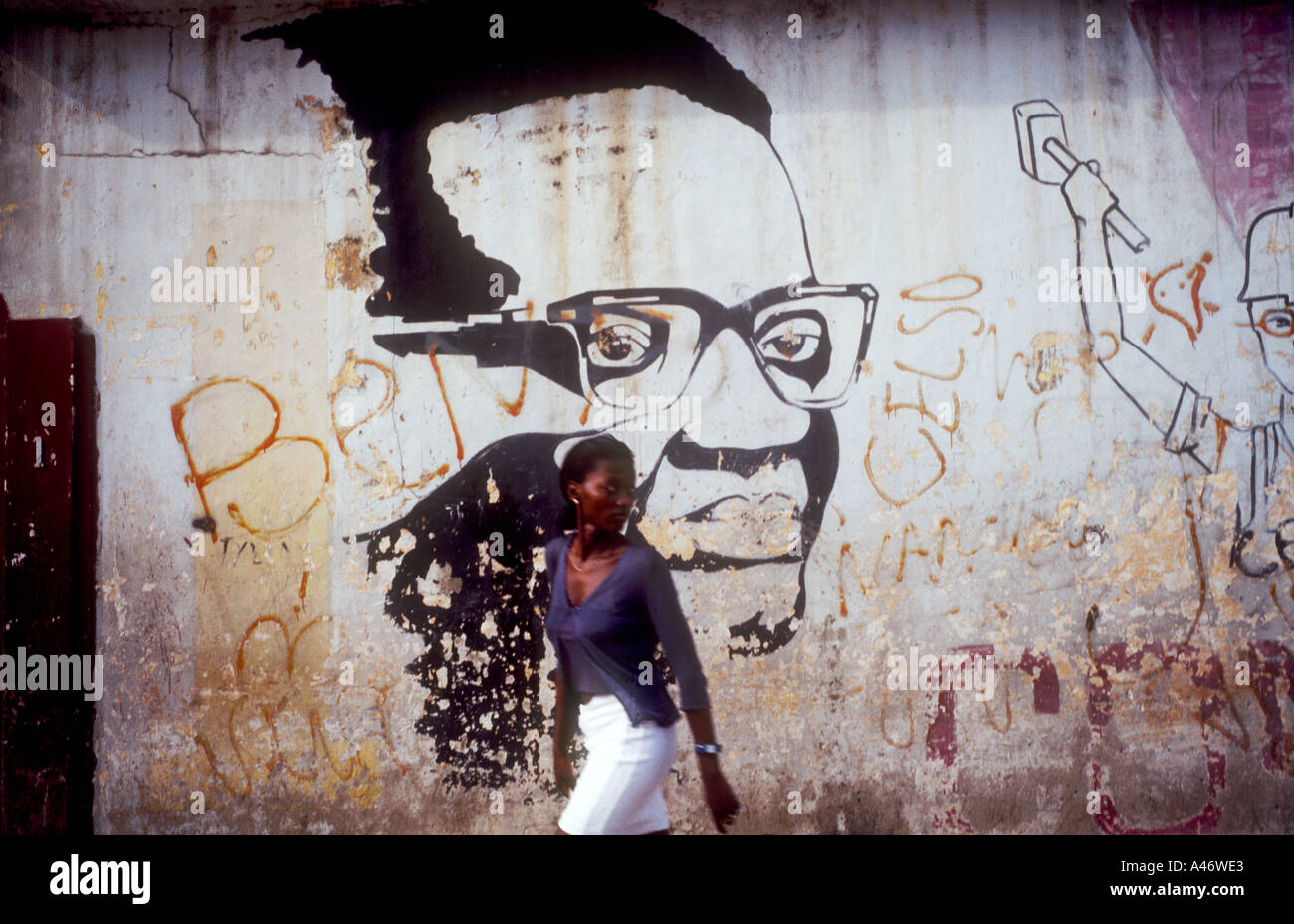 A woman walks in front of a poster of Agostinho Neto a hero of the Angolan Revolution in Luand, Angola - Stock Image