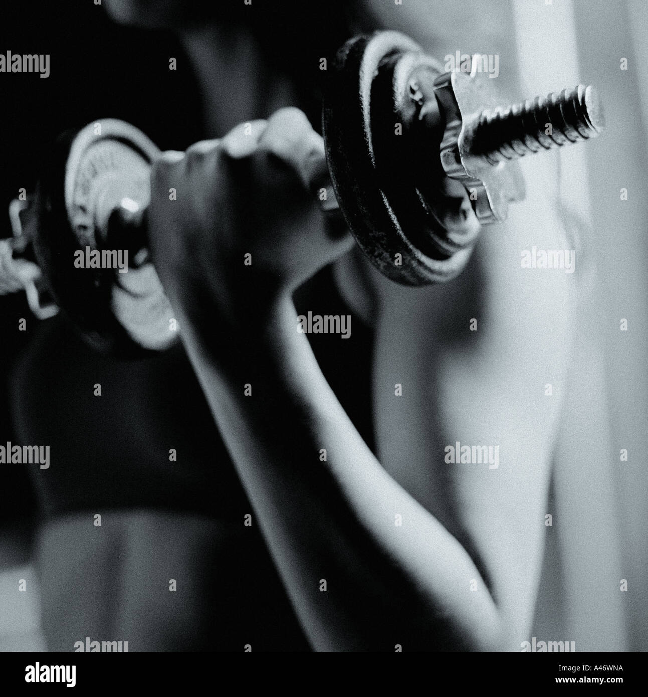 A woman pumping a barbell - Stock Image