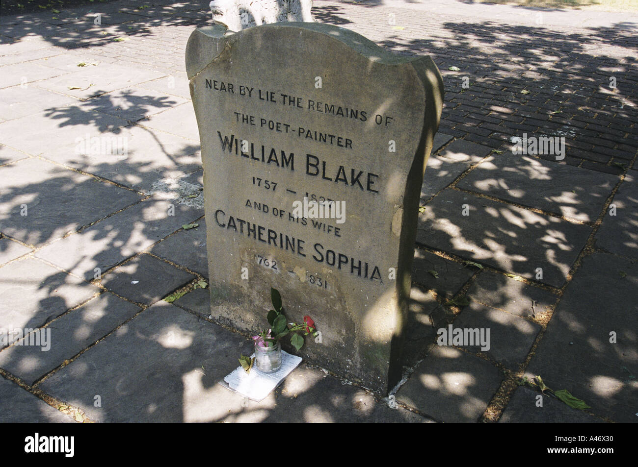 The headstone of William Blake, poet and artist with a flower by the grave in Bunhill Fields, London, UK - Stock Image