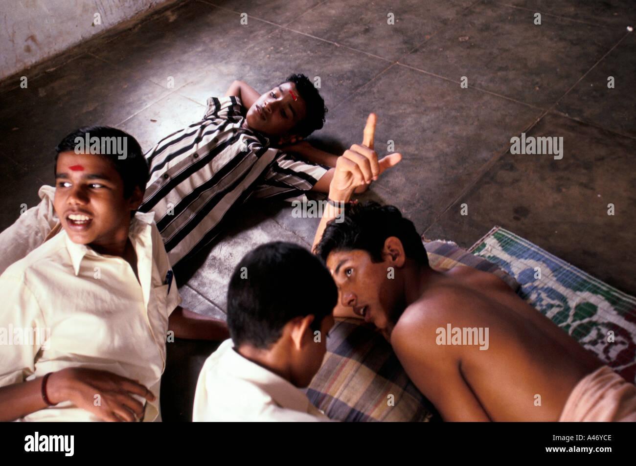 Kathakali students relax on the floor at The Kerala Kalamandalam, the state academy for Kathakali, Kerala, India - Stock Image
