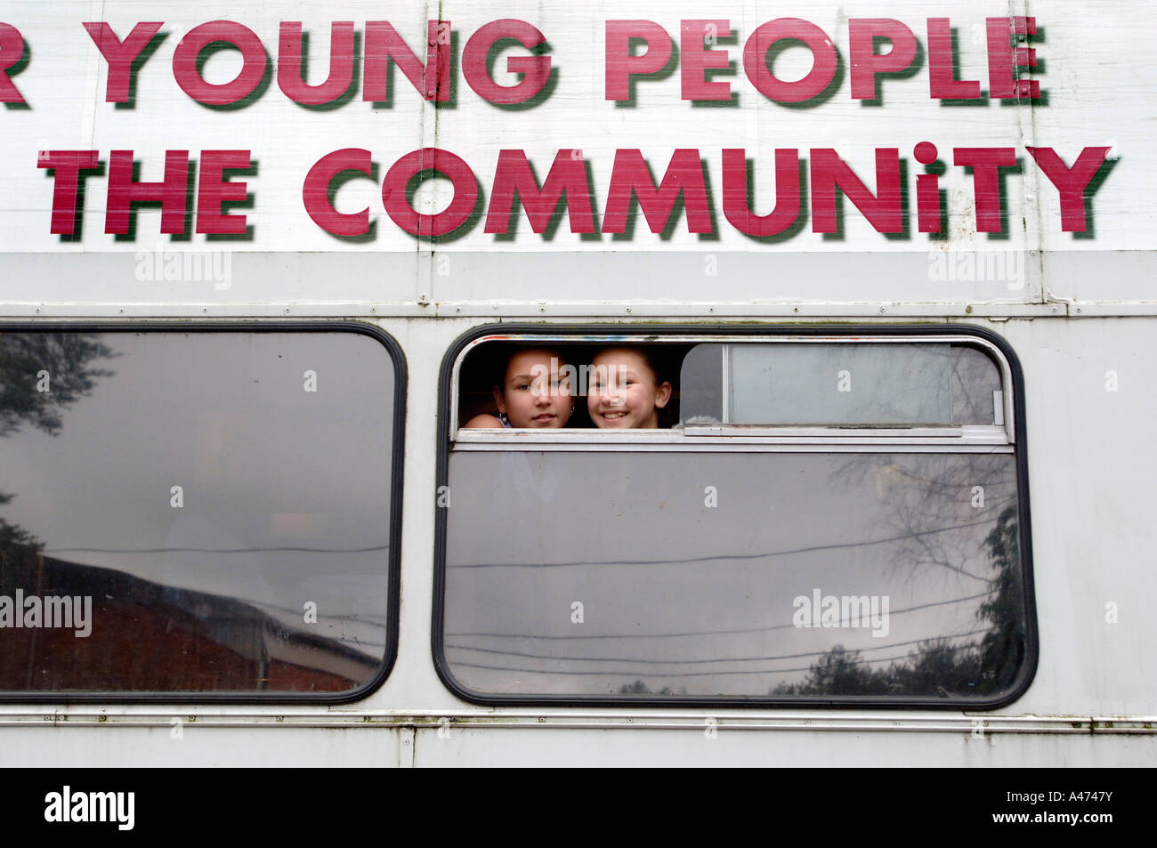 Two cheeky smiling traveller girls look out of the window of a community bus - Stock Image
