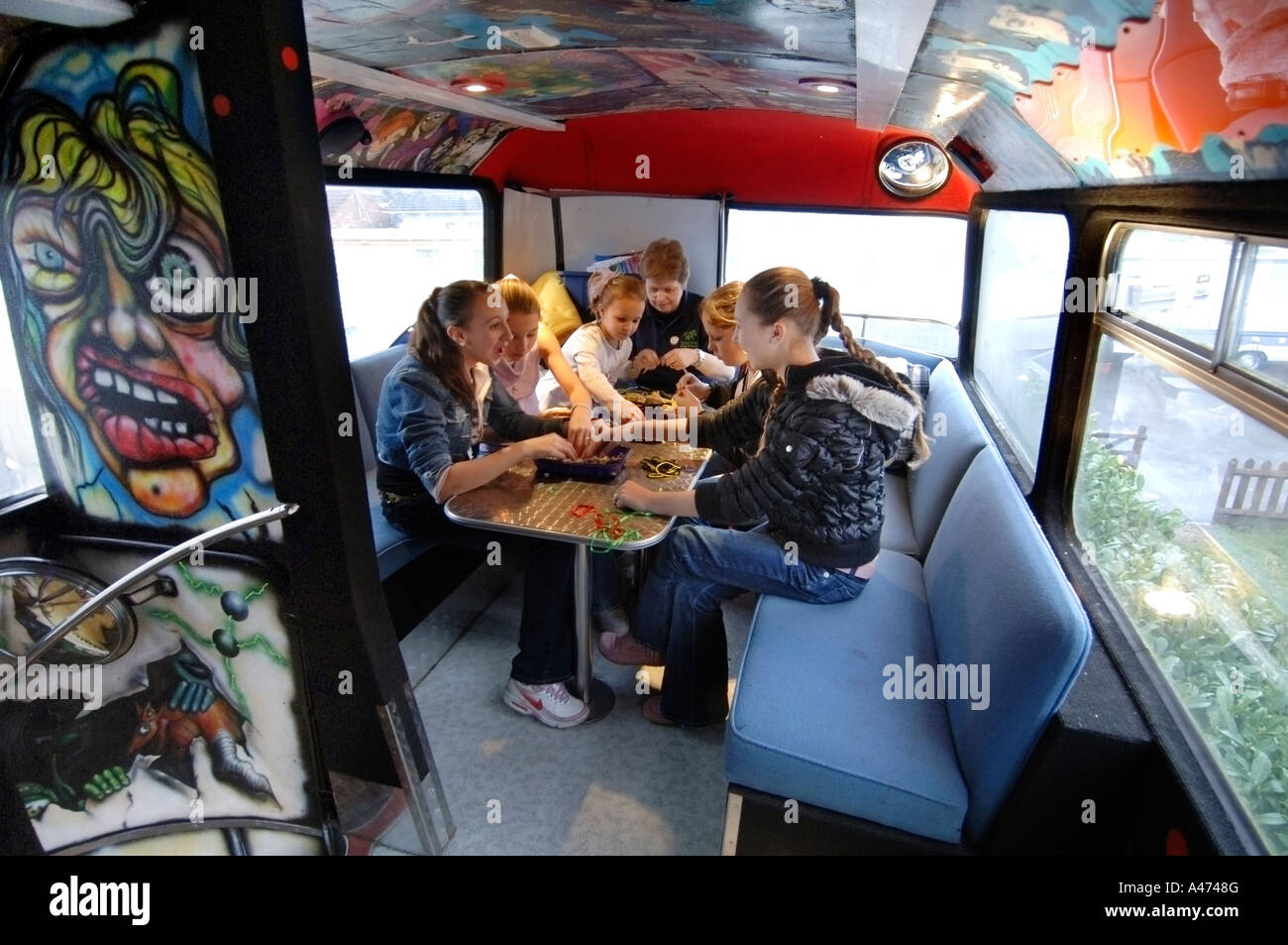 Traveller girls on the double decker community bus used as a classroom at Star Hill Gypsy Site in Hartley Witney, - Stock Image