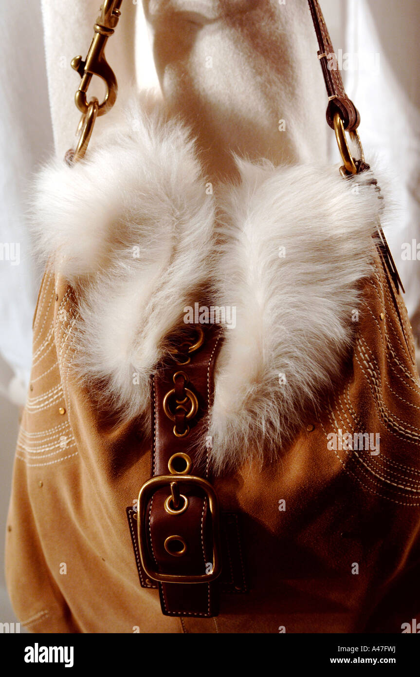 4c701ea14a Store window mannequin with white winter coat holding a fur and brown leather  bag - Stock