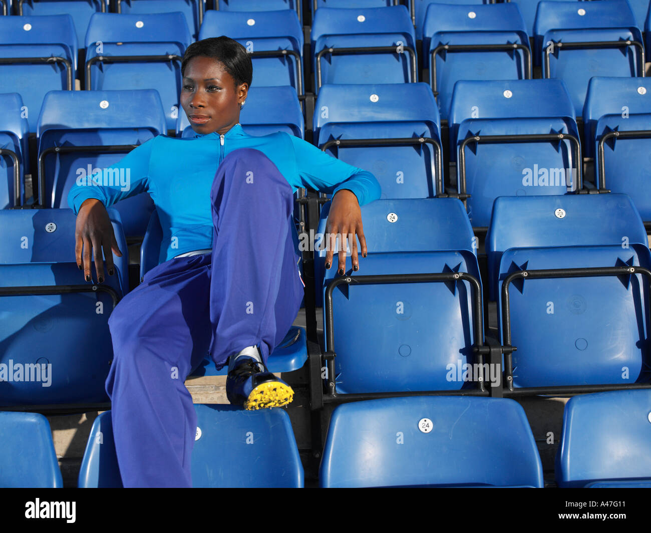 Athlete sitting in empty stadium - Stock Image