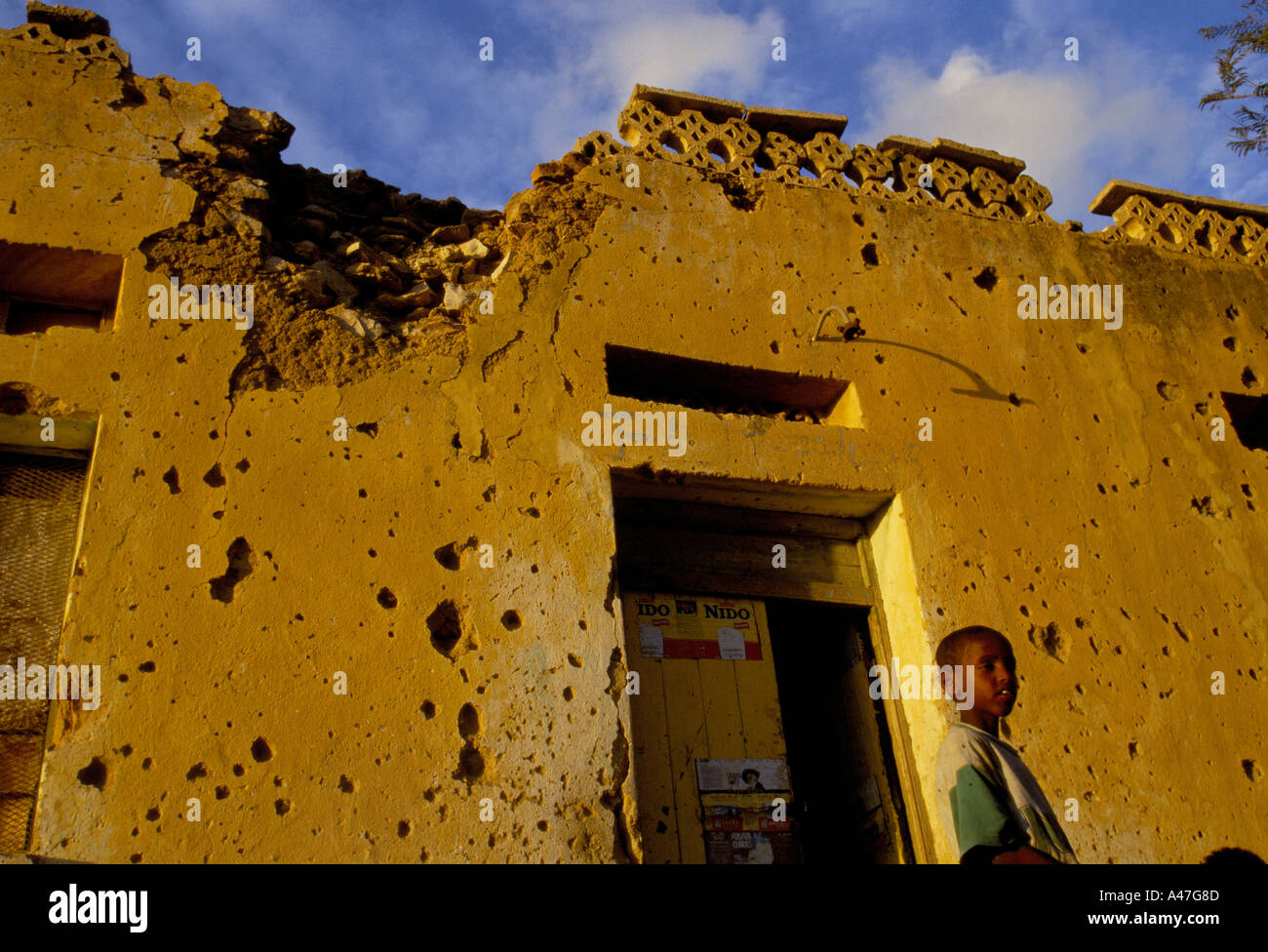 A child outside his house that clearly shows war damage from the battle for Hargeisa Somaliland - Stock Image