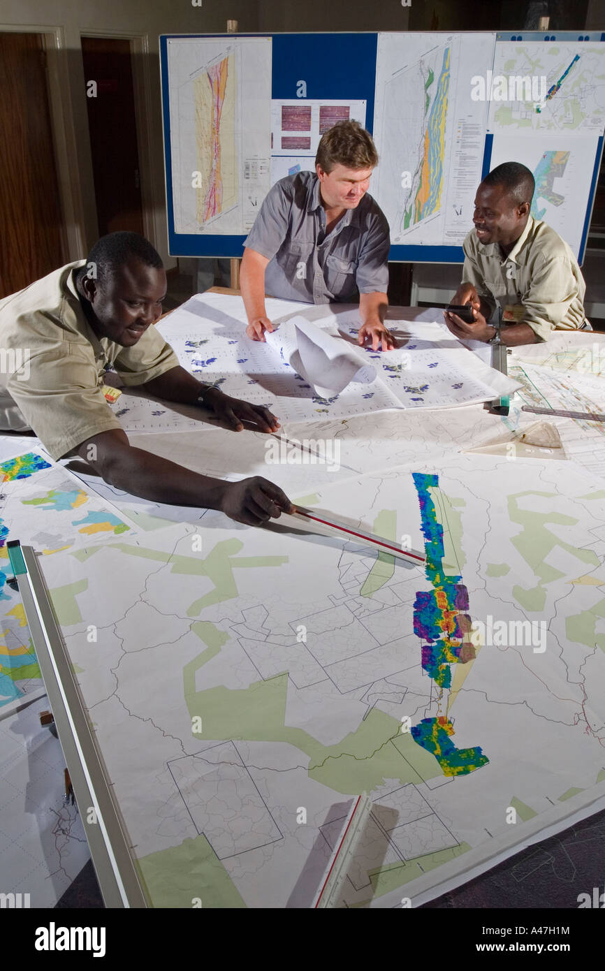 Geologists examining maps and discussing exploration targets, geology department, gold mine, Ghana, W Africa - Stock Image