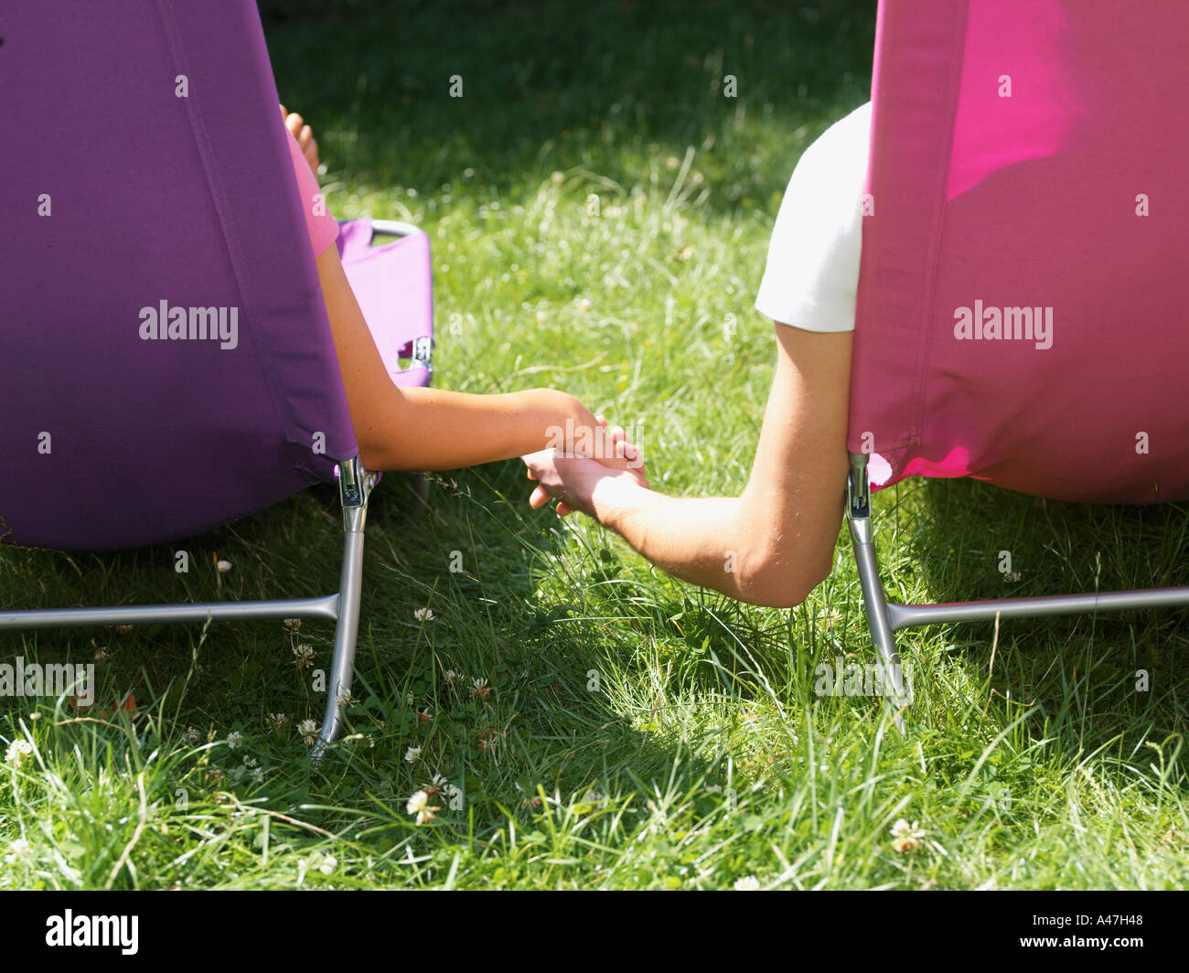 Young couple relaxing on lounge chairs Stock Photo