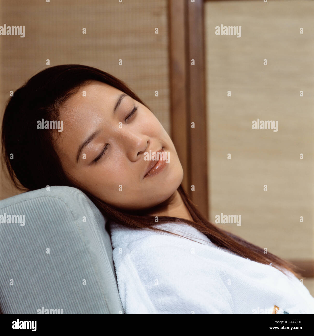 Asian woman sleeping in armchair - Stock Image