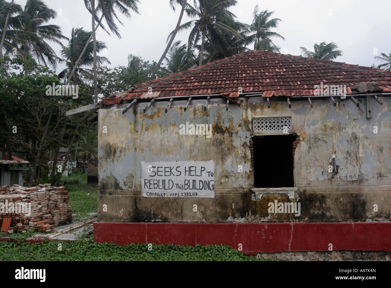 The owners of a damaged house have placed a poster to ask for help with the reconstruction of their house in Sri - Stock Image