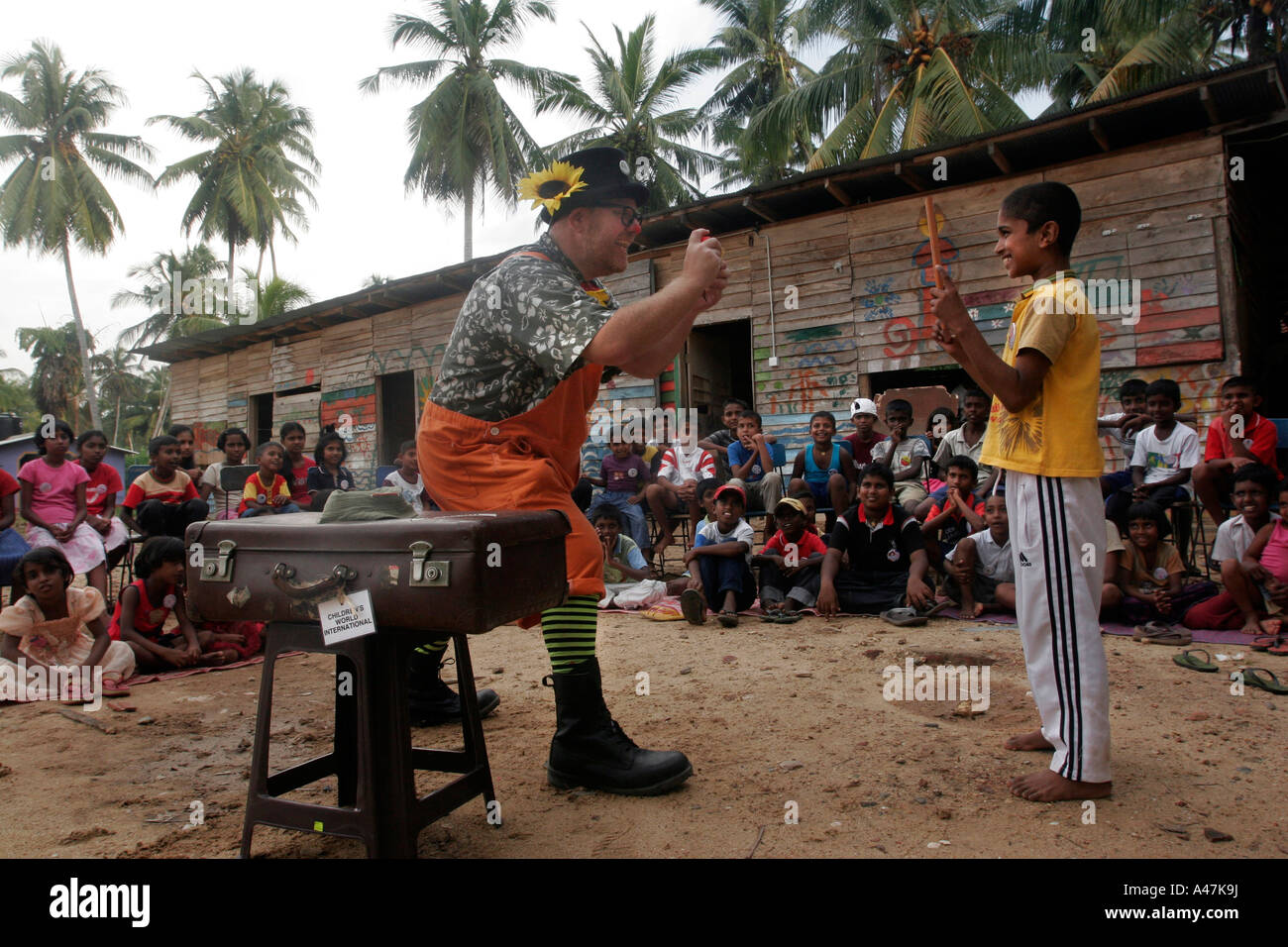 A clown performs for children living in a tsunami relief camp in the village of Paraliya in southern Sri Lanka. - Stock Image