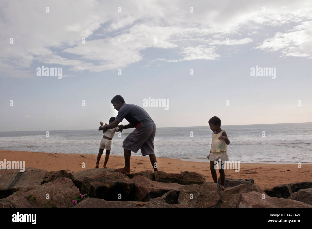 A father and his twin daughters visit the beach everyday to cherish the memory of their family members who died Stock Photo