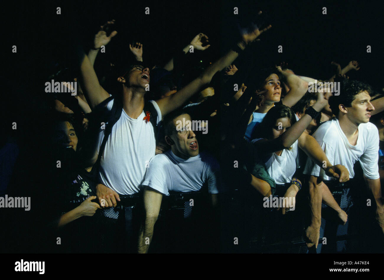 u2 on tour june 1993 pop group u2 on tour enraptured fans at front of stage reach towards band during concert - Stock Image