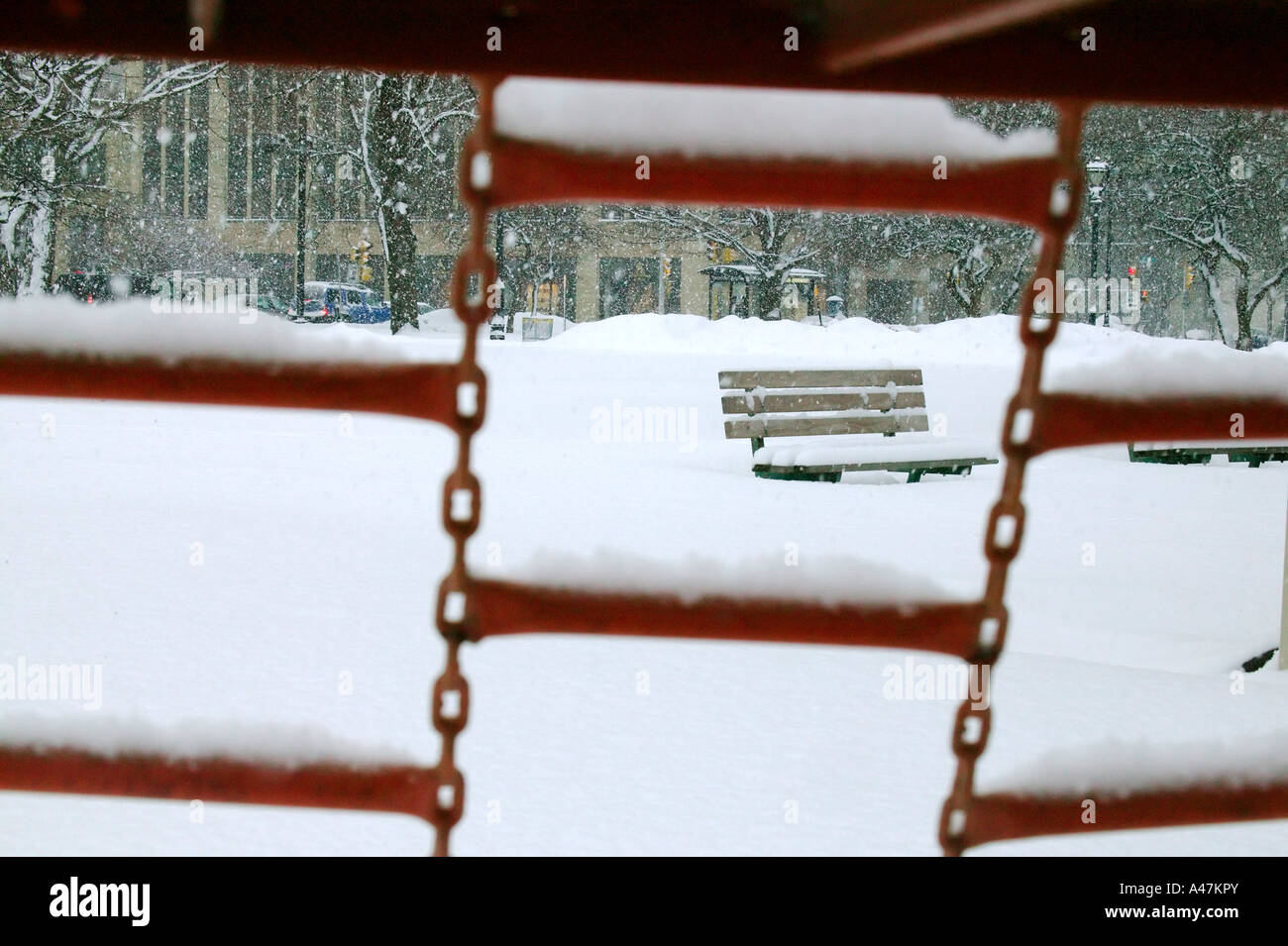 Park bench in the snow seen through play structure steps - Stock Image