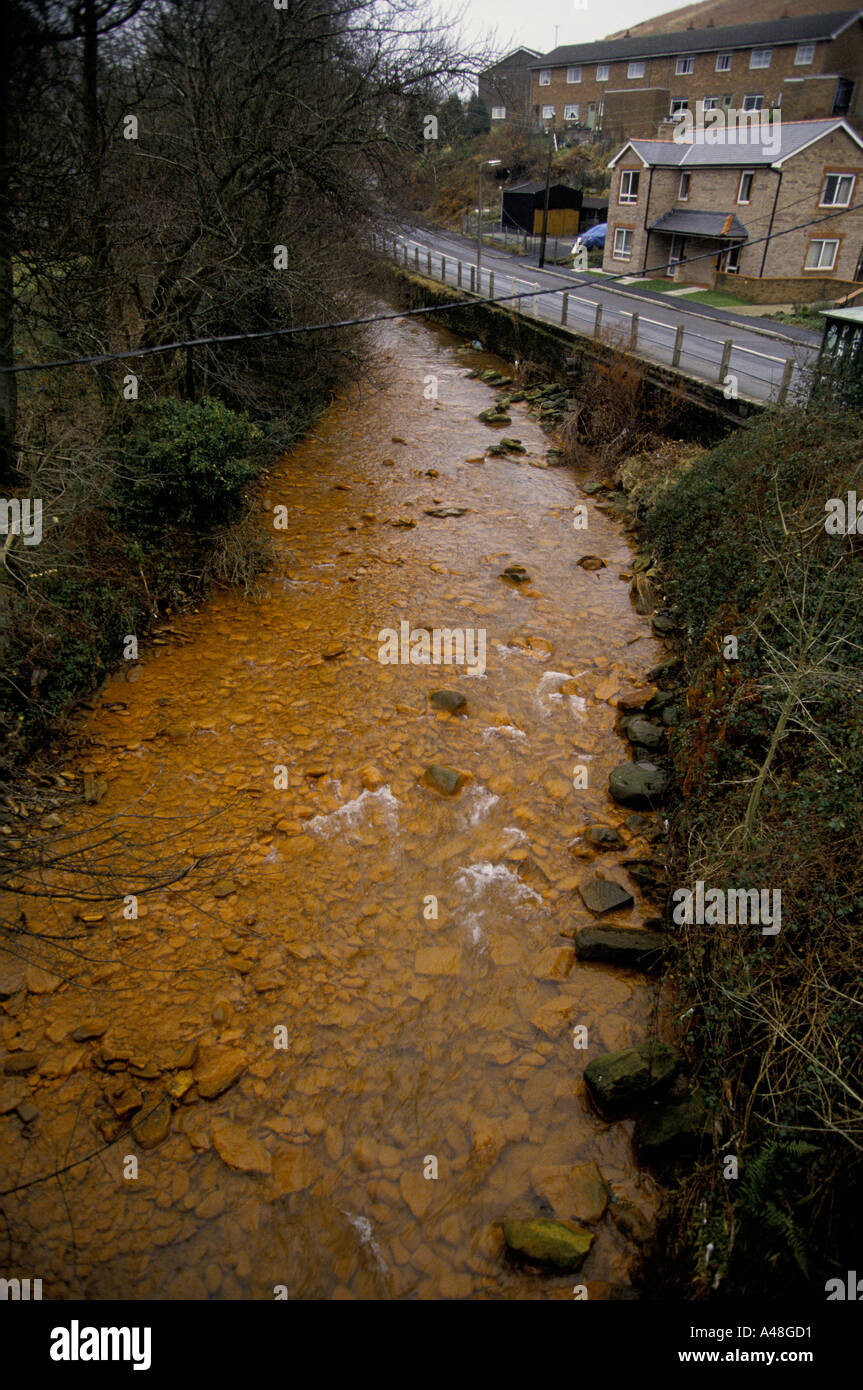 iron seepage at disused coal mine into river pelena near port talbot south wales - Stock Image