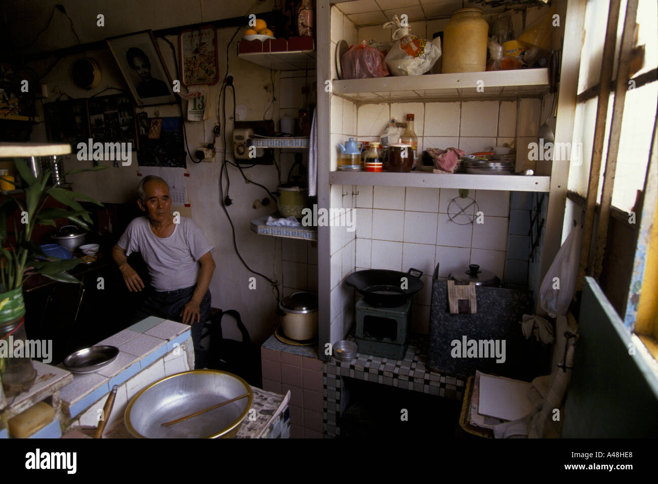 man in kitchen of his tvery small flat in kowloon hong kong - Kowloon Kitchen