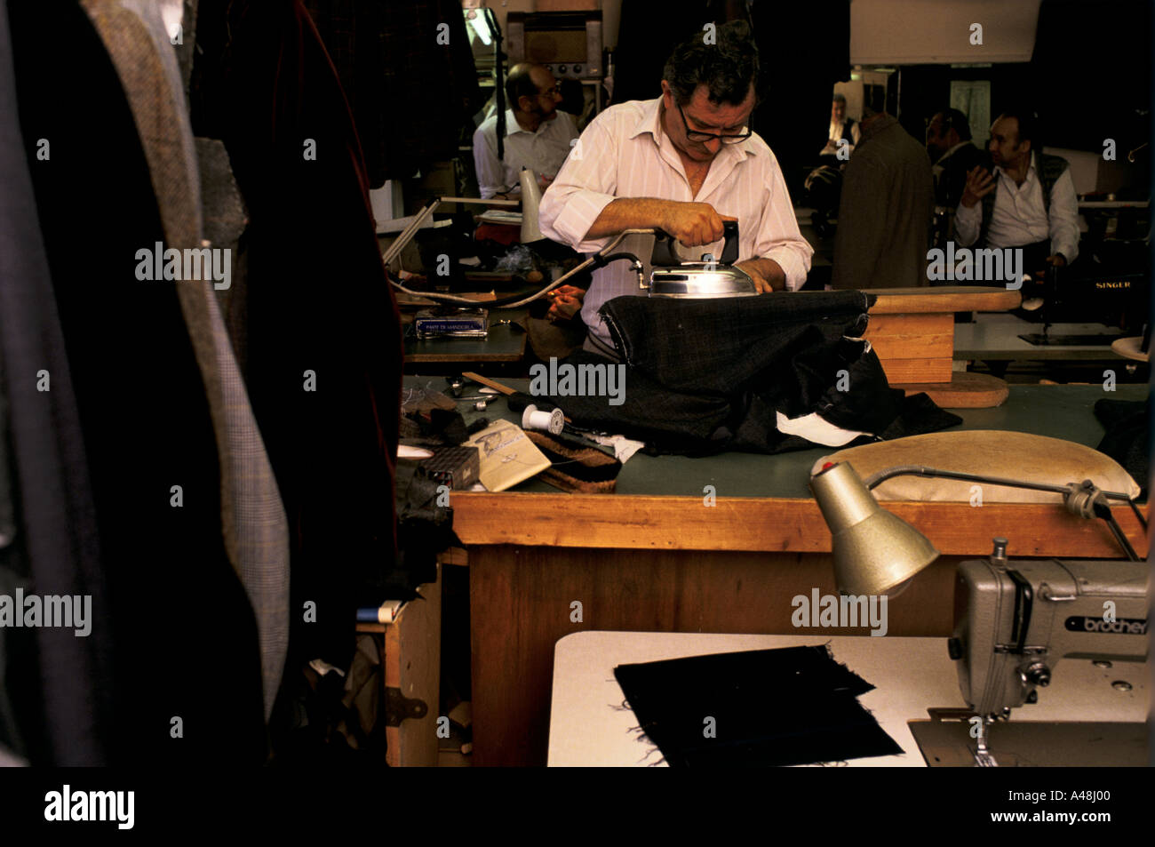 saville row tailor in his shop and workshop - Stock Image