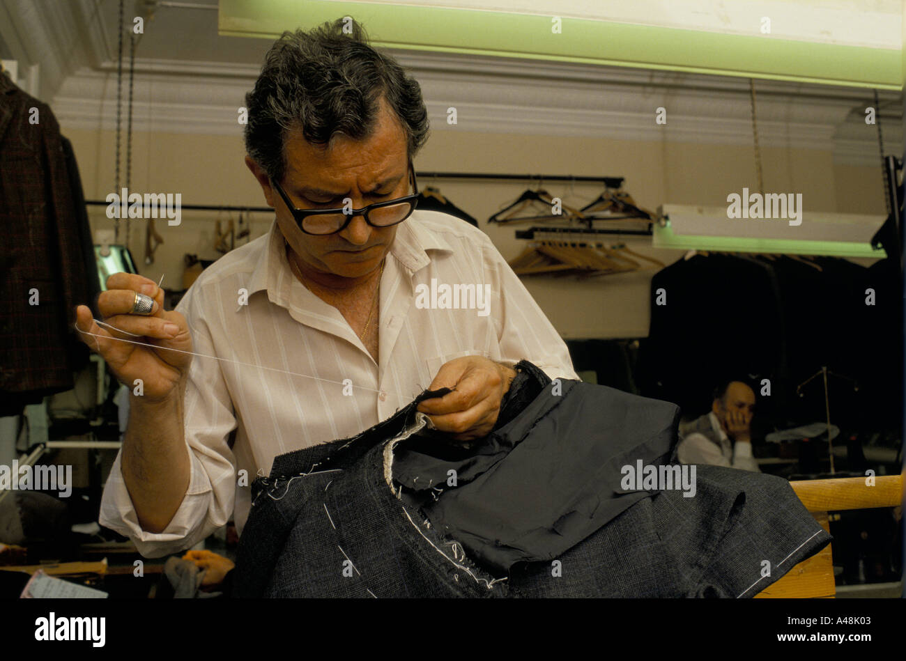 A tailor sewing up a suit in a shop in Saville Row - Stock Image