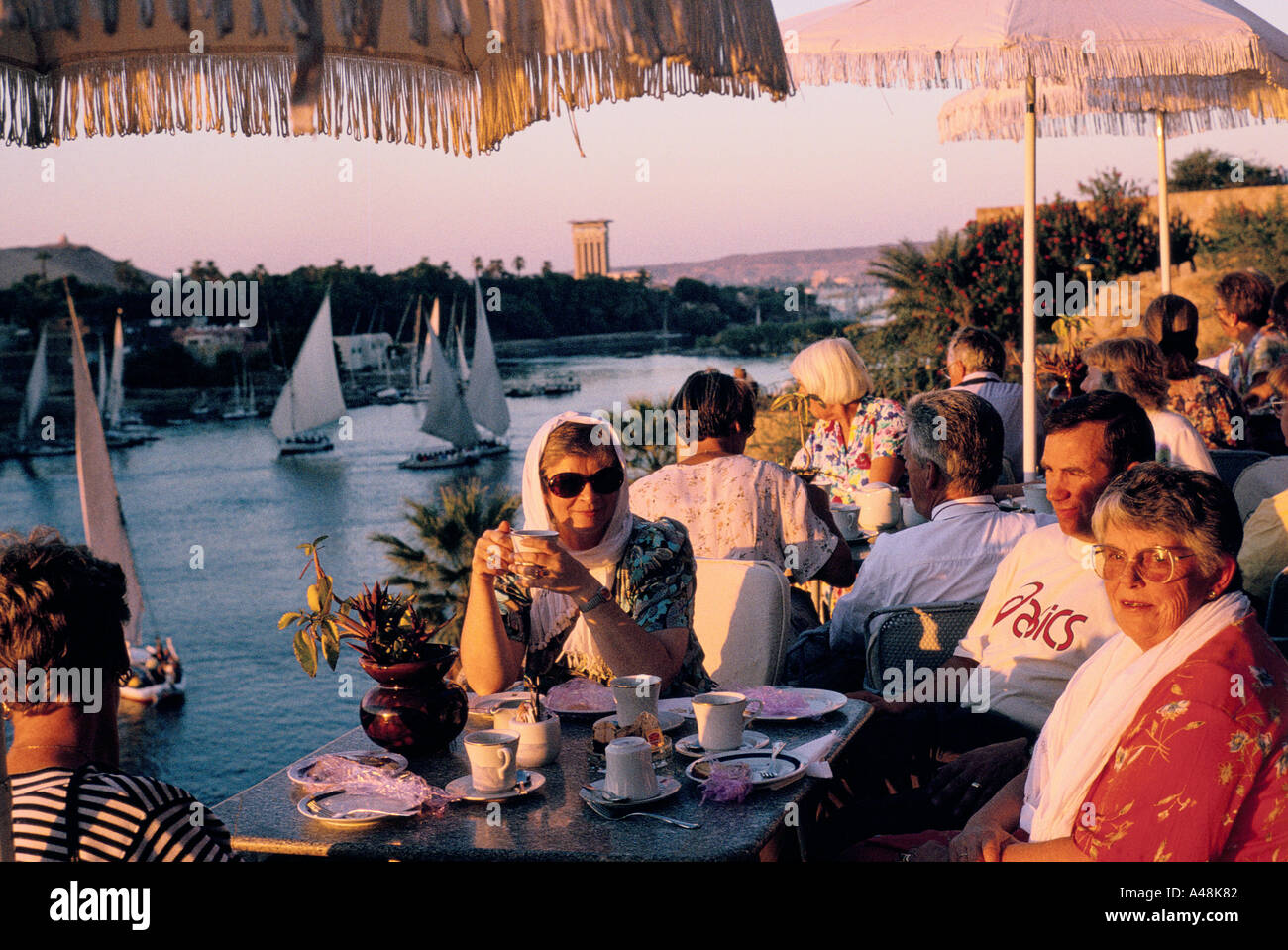 Tourist having afternoon tea on the terrace of The Old Cataracts Hotel over looking th River Nile at Aswan - Stock Image