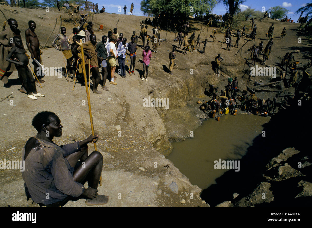 Hungry displaced Dinka and Tuposa people around a waterhole in Naruse Southern Sudan 1986 - Stock Image