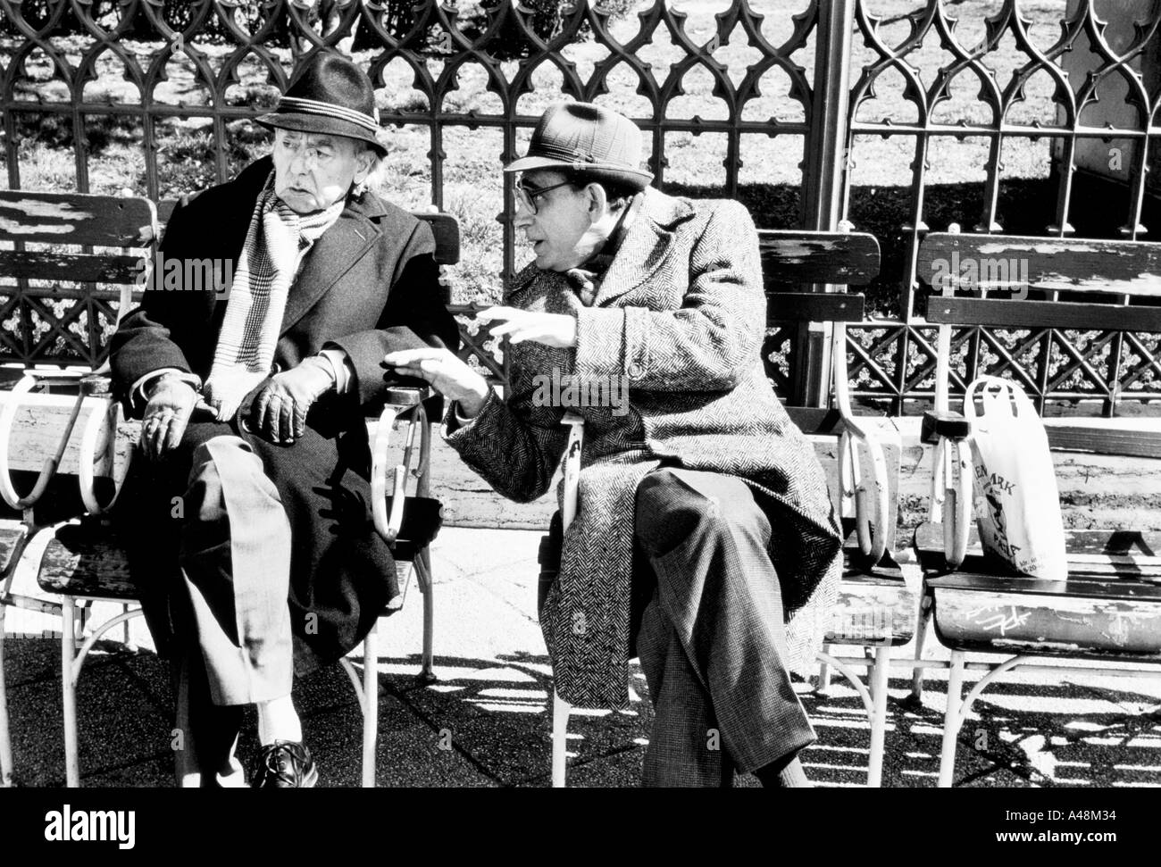 two older men talking and enjoying the spring sunshine on the esplanade beside the Danube in Budapest Stock Photo