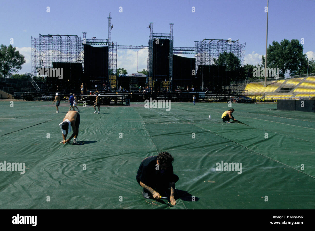 Roadies preparing a stadium for a concert by Irish rock band U2 lay protective covering over the football pitch. - Stock Image