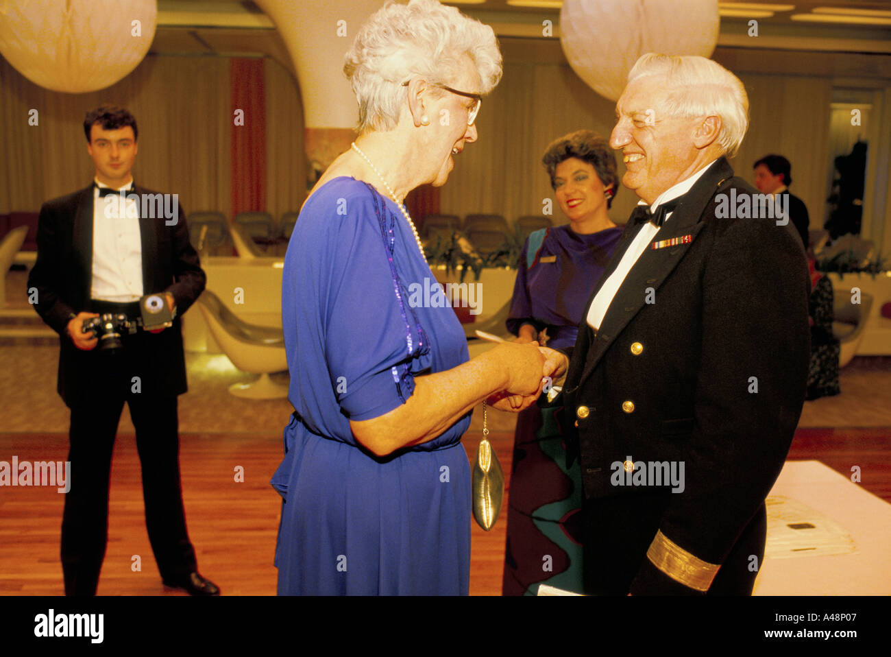 Captain of The cruise liner QE2 meeting passengers at his coctail party before crossing the atlantic - Stock Image