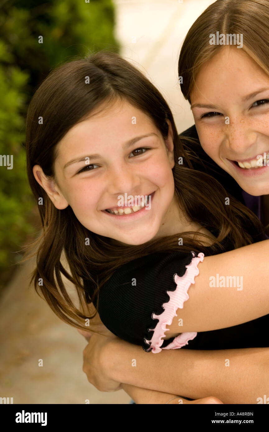 Girl embracing sister, smiling, portrait - Stock Image