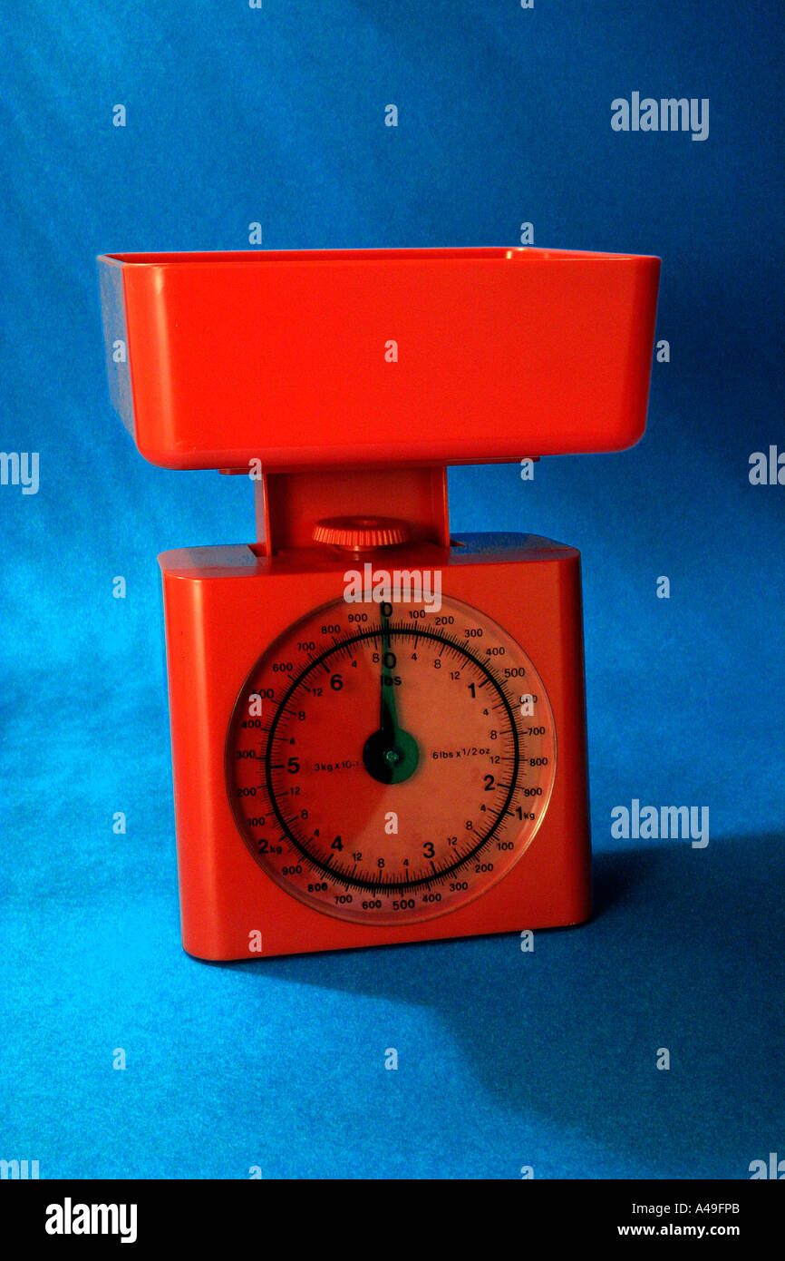 red kitchen scales on blue background - Stock Image