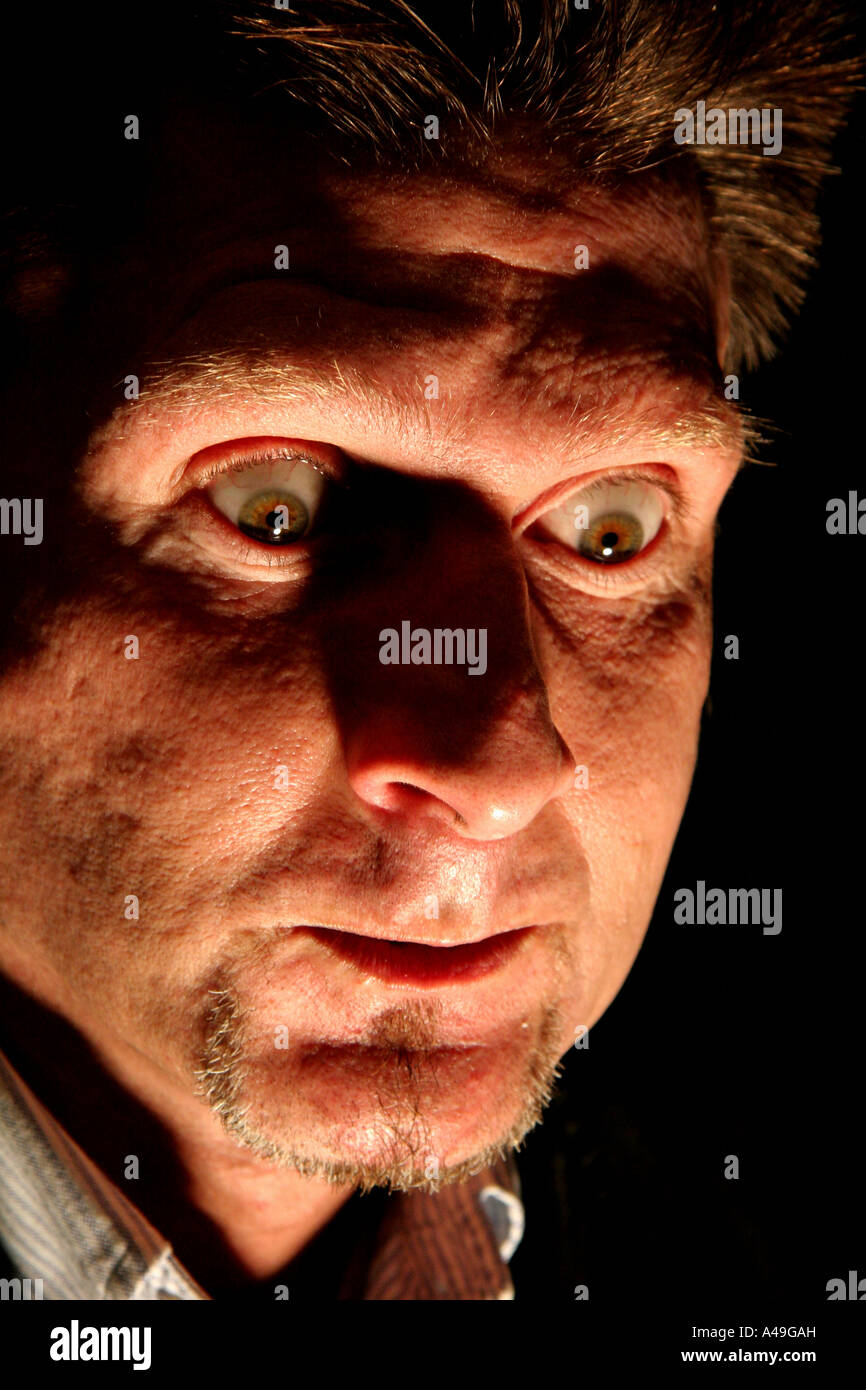Man with a frightening look on his face - Stock Image