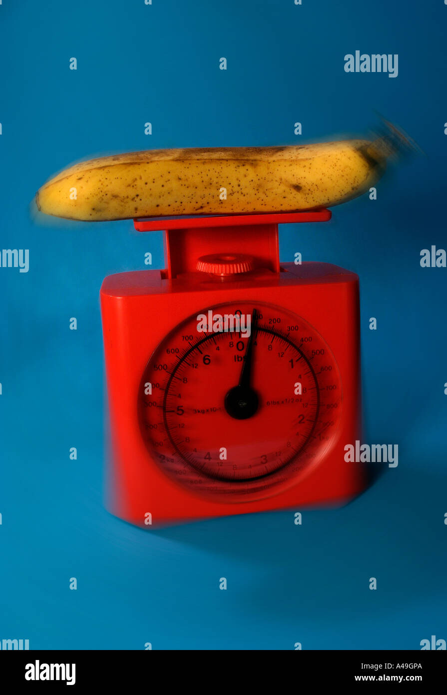 banana on red scales - Stock Image