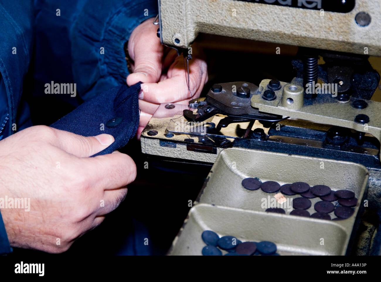 Man operating a Lock stitch Button machine Manchester UK - Stock Image