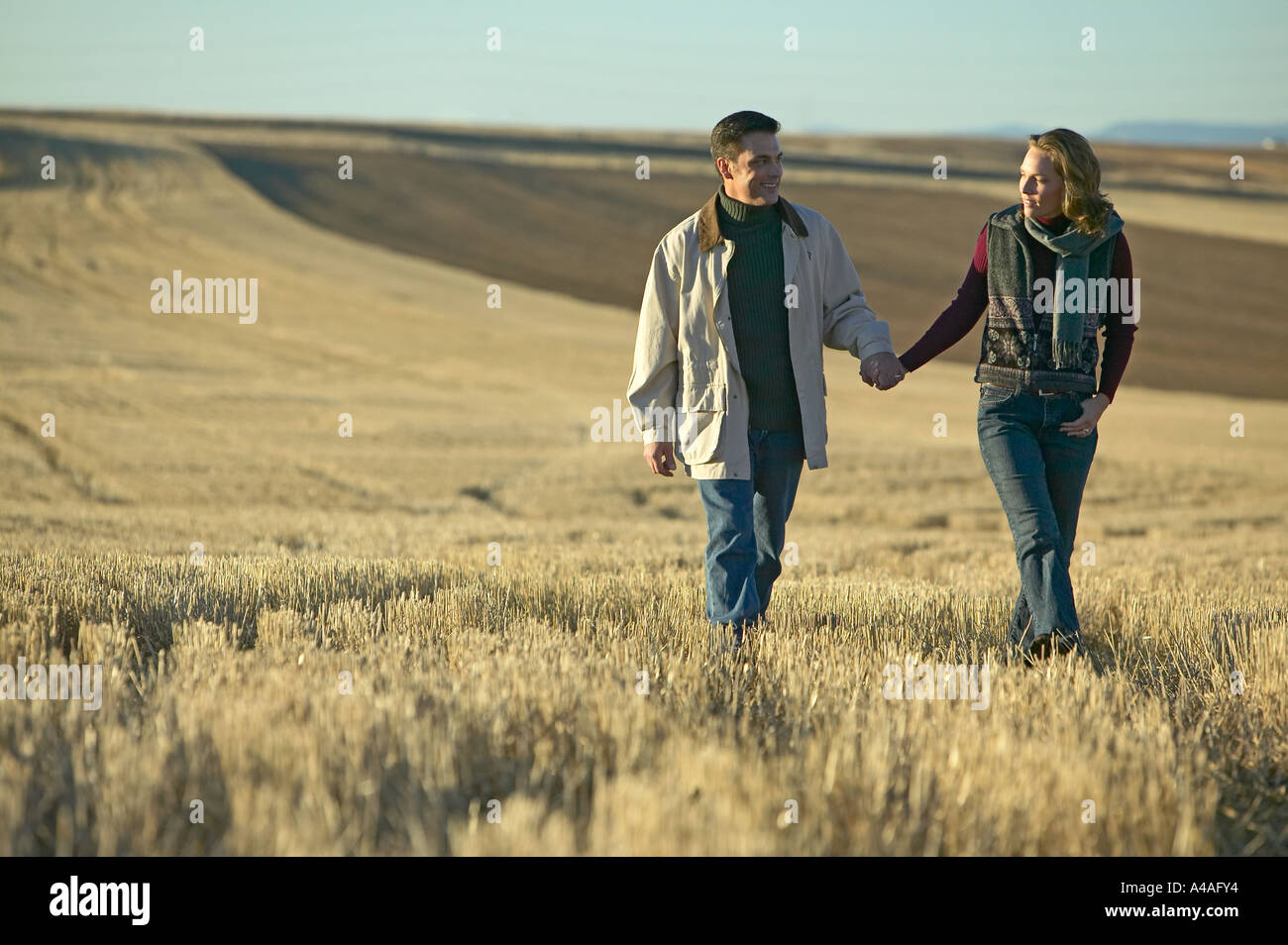 Couple walking through fields of cut grass in Fall Colorado early morning Stock Photo