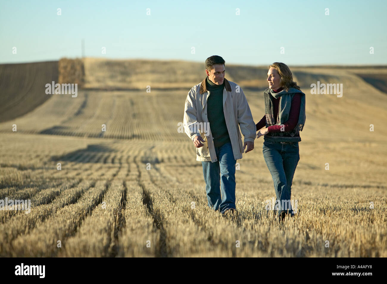 Couple smiling walking through fields of cut grass in Fall Colorado early morning Stock Photo