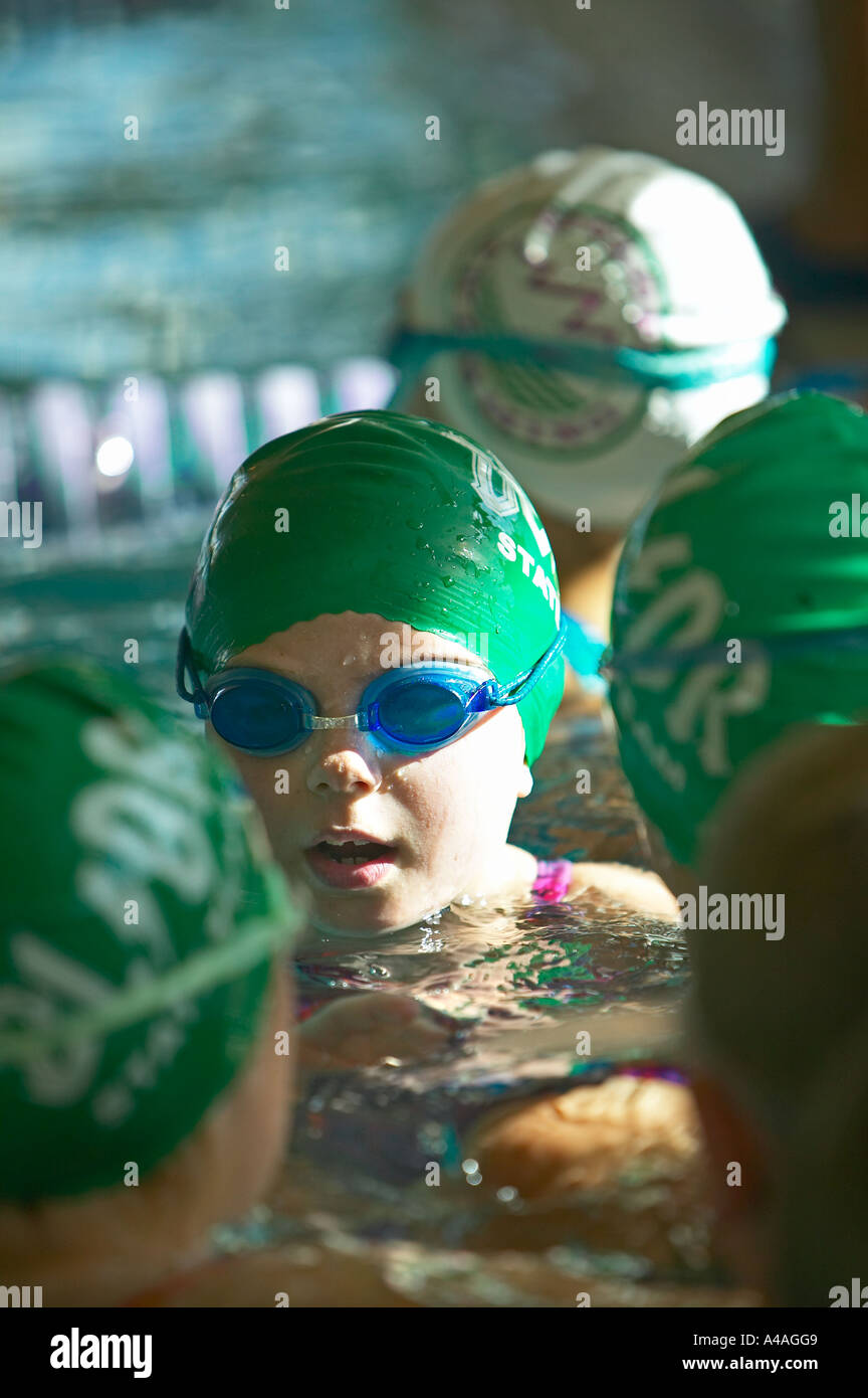 Girl in goggles and green cap at indoor swimming practice meet - Stock Image