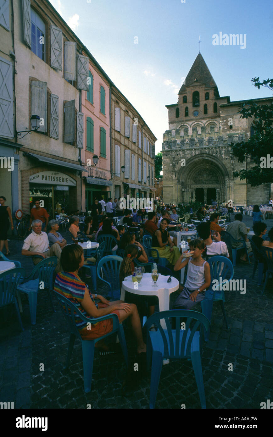 France. Moissac. Cafe customers sit in front of Abbey St. Pierre in the evening. Stock Photo