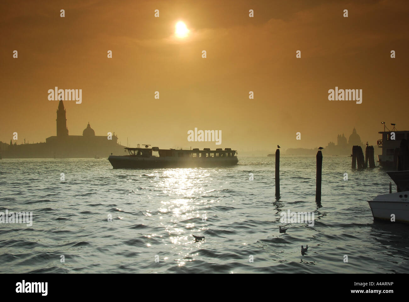 A vaporetto leaves its mooring on the Canale Di San Marco in Venice with the chuch of San Giorgio Maggiore across - Stock Image