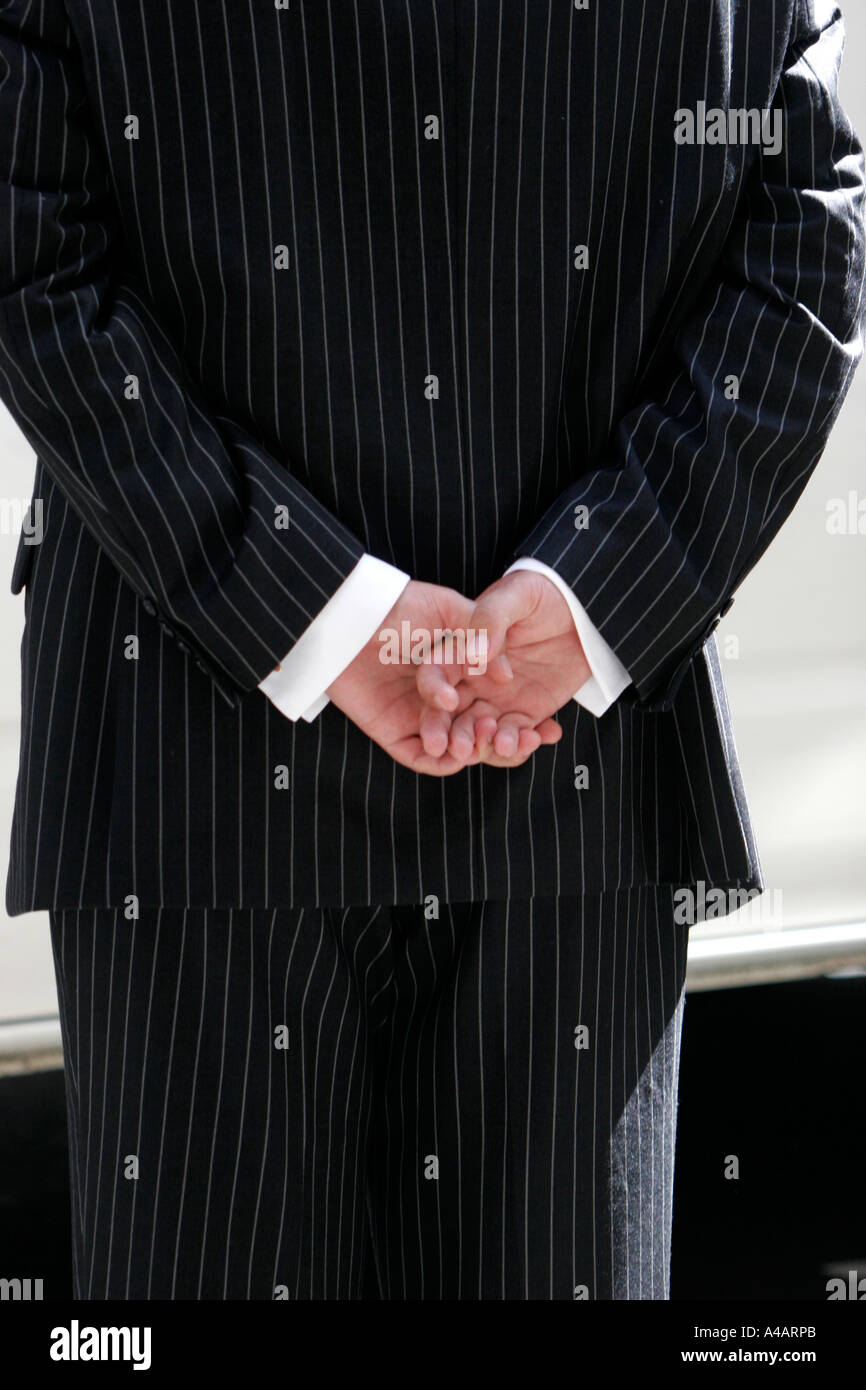 Man in pin stripe suit with hands behind his back - Stock Image