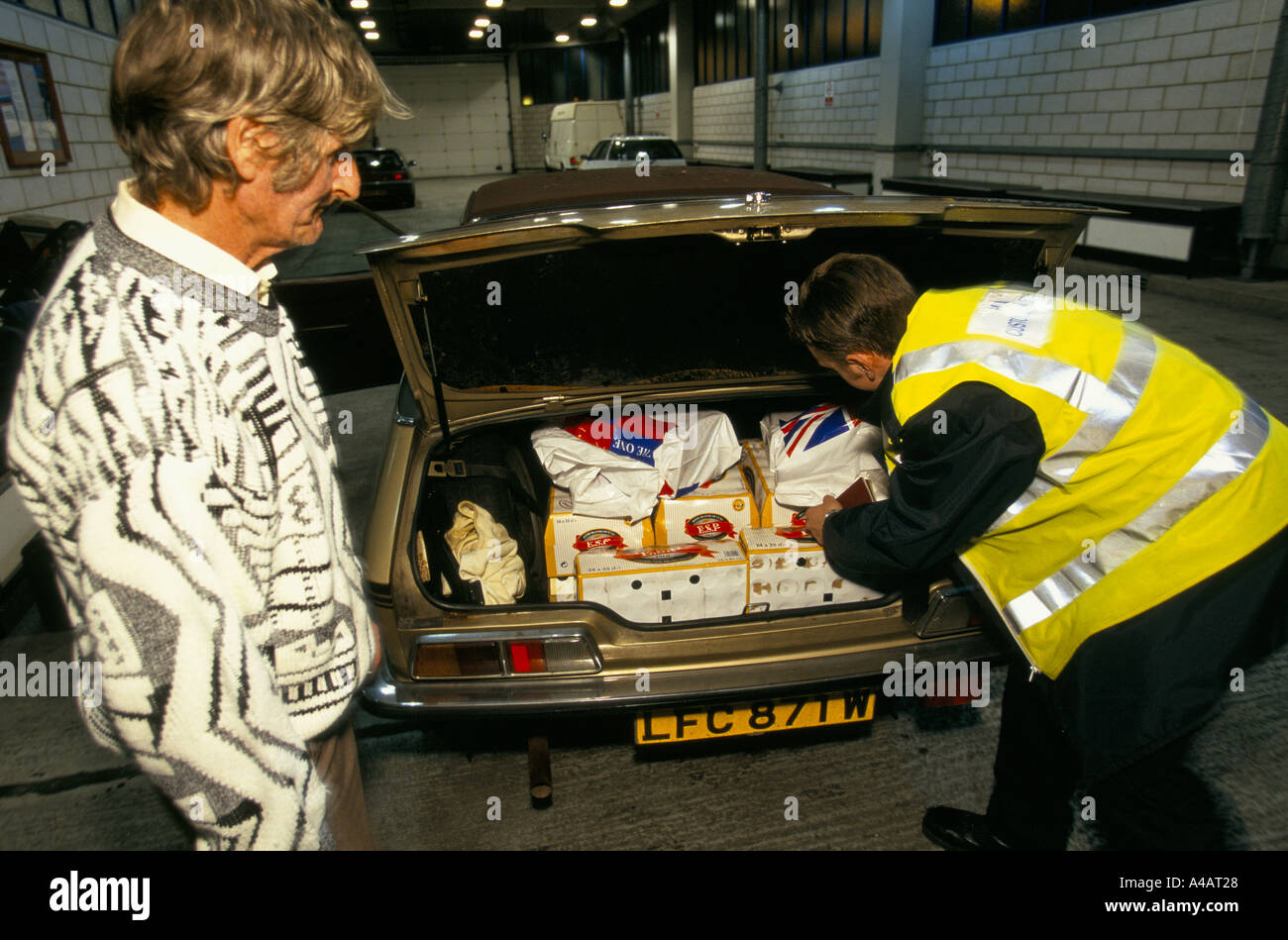 A CUSTOMS & EXCISE OFFICER AT  DOVER PORT ON ENGLAND'S SOUTH COAST CATALOGUES GOODS BEING CONFISCATED FROM A SMUGGLER. - Stock Image