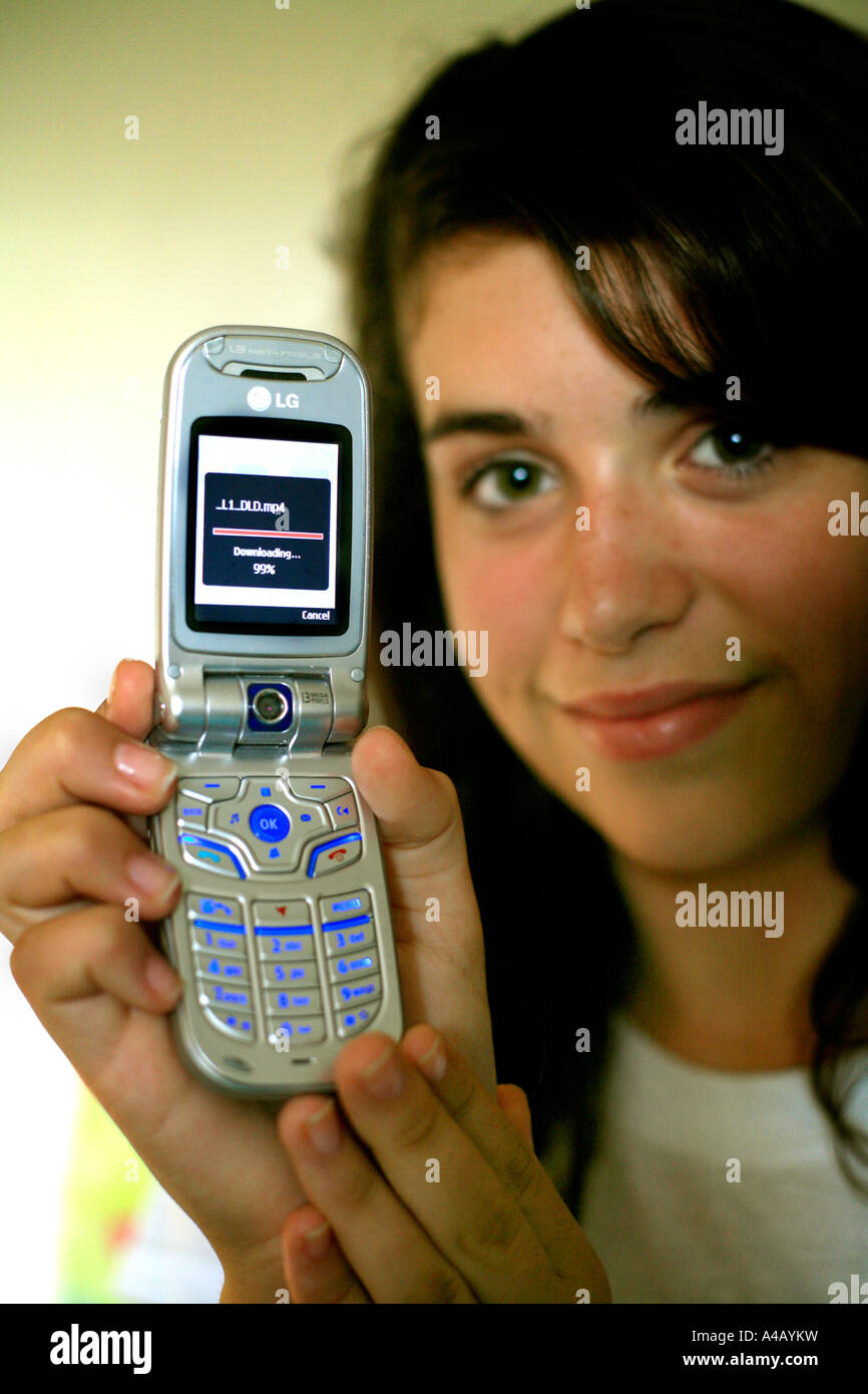 A Teen Girl Downloads A Music Video Onto A 3g Capable Mobile Or Cell