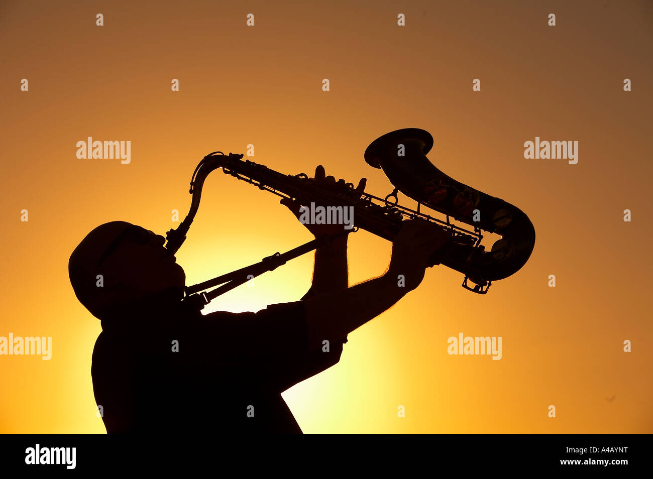 Silhouette of man playing the saxophone - Stock Image