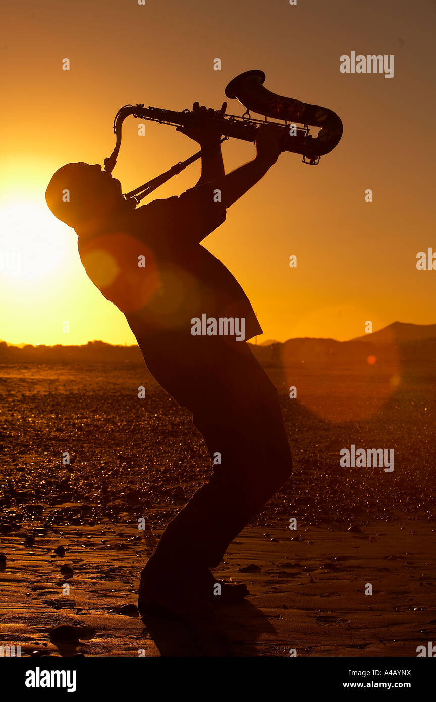 Silhouette of man playing the saxophone at  sunset - Stock Image