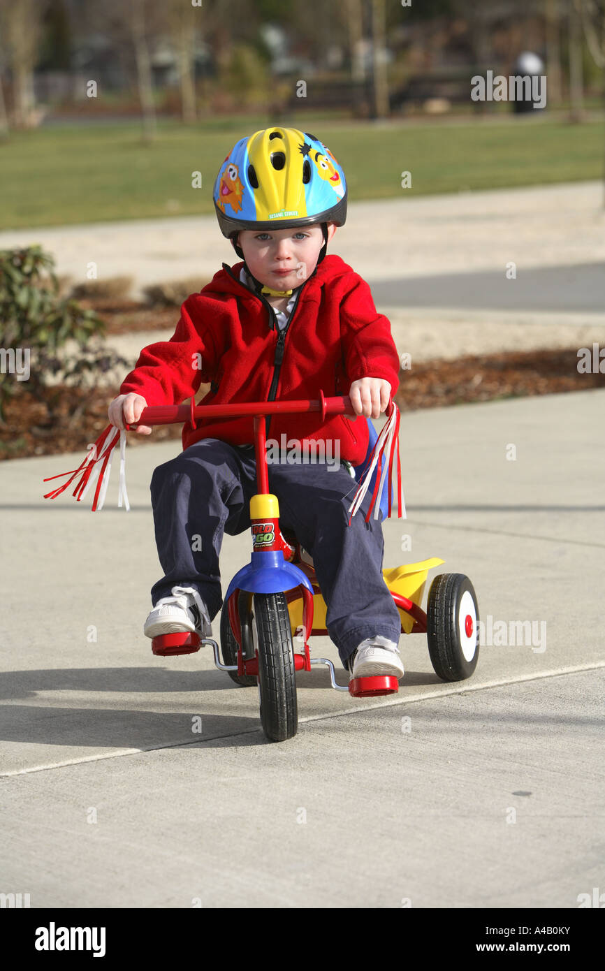 Two year old boy riding a tricycle. - Stock Image